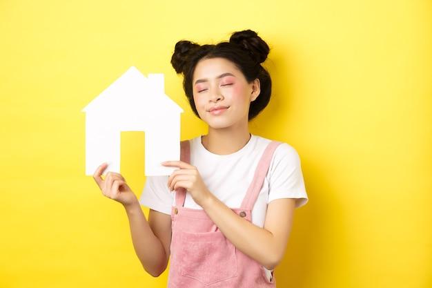 不動産と家族の概念。明るい化粧をした夢のような笑顔のアジアの女性、目を閉じて紙の家の切り欠きを示し、不動産の購入について空想にふける、黄色。