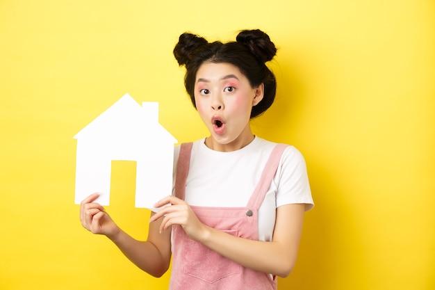 不動産と家族の概念。紙の家の切り欠きを見せて、黄色の上に立って驚いてあえぎながら興奮しているアジアの十代の少女。