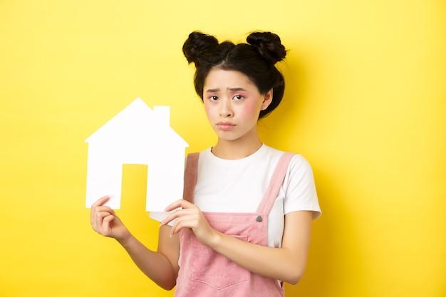 不動産と家族の概念。明るい化粧、眉をひそめ、怒って、紙の家の切り欠きを示し、黄色の上に立っている悲しいかわいいアジアの女の子。