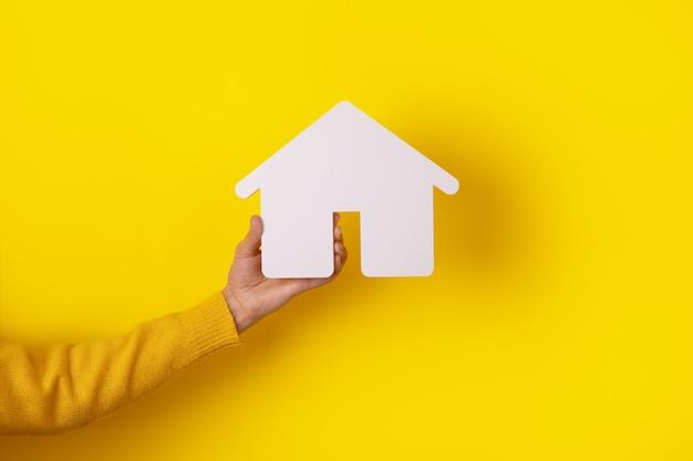 부동산 및 가족 주택 개념, 노란색 배경 위에 손에 집