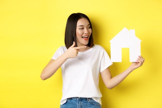 不動産と保険の概念。笑顔、指差し、紙の家の切り欠きを見て、黄色の背景の上に立って、代理店のロゴをお勧めします。