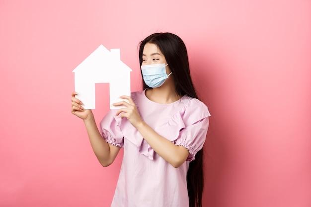 부동산 및 유행병 개념. 분홍색 배경에 서있는 속성을 구입, 종이 집 컷 아웃 기쁘게 찾고 의료 마스크에 아시아 여자를 흥분.