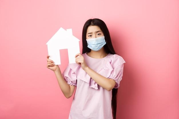 부동산 및 유행병 개념. 분홍색 배경에 서있는 의료 마스크와 드레스를 입고 종이 집 컷 아웃을 보여주는 우울한 소녀.