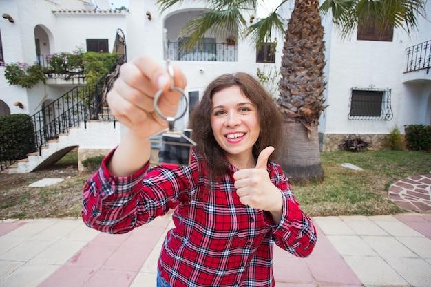 부동산 및 재산 개념. 행복한 소유권. 매력적인 젊은여자가 동안 키를 들고