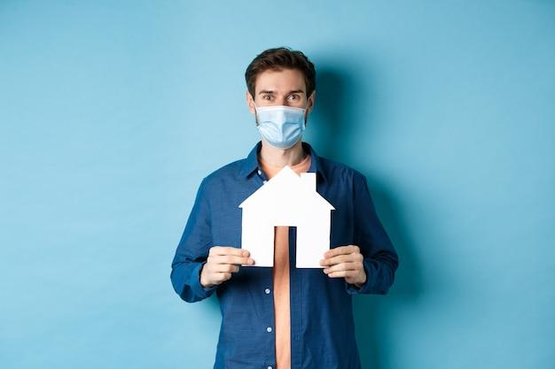 부동산 및 검역 개념. 집 컷 아웃을 보여주는 의료 마스크, 재산을 구입, 파란색 배경에 서있는 행복 한 젊은 남자.