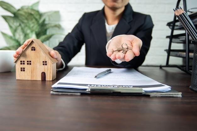 不動産とサイン契約、住宅の売り手と買い手が交渉に成功し、合意に達し、所有者に家の鍵を渡す