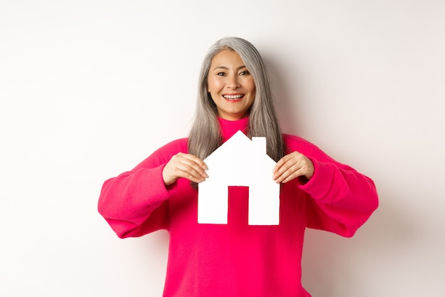 Real estate beautiful asian grandmother showing paper house and smiling happy standing in pink sweat...