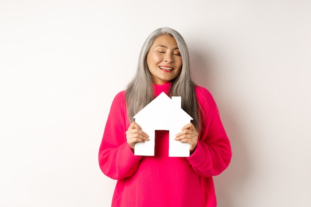 不動産。目を閉じて紙の家のモデルを抱き締め、アパートを買うことを夢見て笑って、白い背景の上に立っている美しい夢のようなアジアの女性