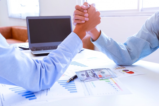 Real estate broker and customer shaking hands after signing a contract.