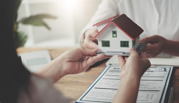 부동산 중개인은 보험, 구매-판매 협상 및 투자 계획 개념으로 집을 구입한 고객에게 집을 제공했습니다.