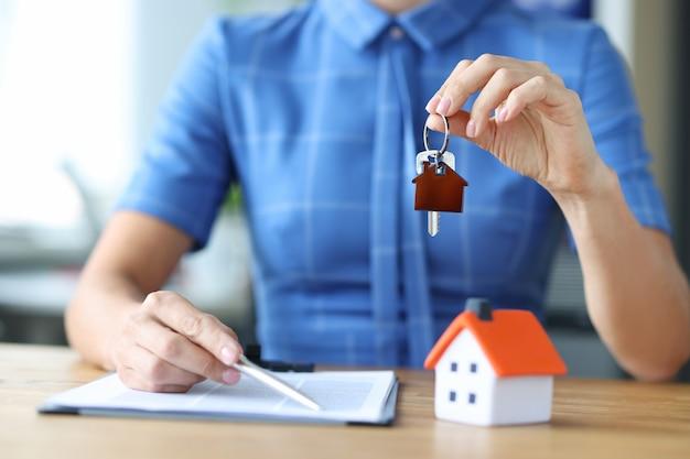 Брокер по недвижимости держит ключ от дома, заключение договора купли-продажи жилья.