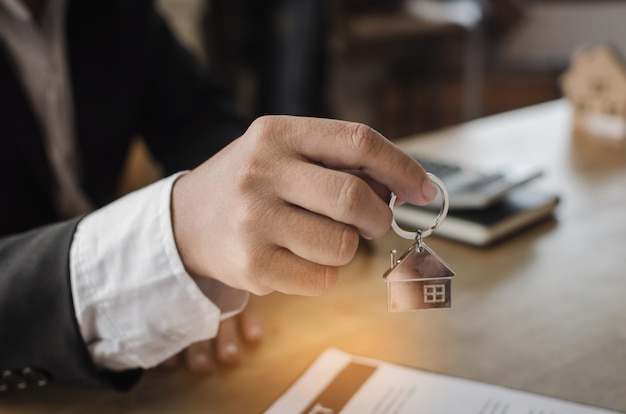 Real estate broker manager giving house key to customer after signing contract