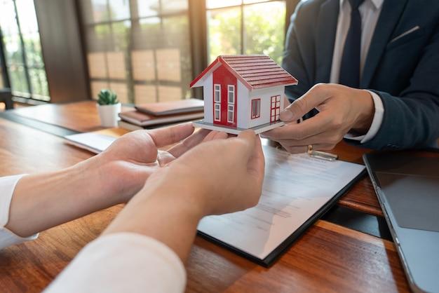 Брокер по недвижимости или агент по продаже, консультирующий клиента по поводу покупки дома, подписывает договор