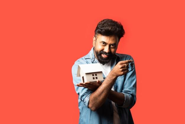 Покупка недвижимости и концепция людей. индийский бородатый мужчина с миниатюрной моделью дома, ключами и копилкой на красном
