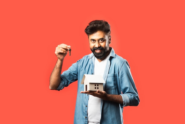 Real estate buying and people concept. indian bearded man with miniature house model, keys and piggy bank on red