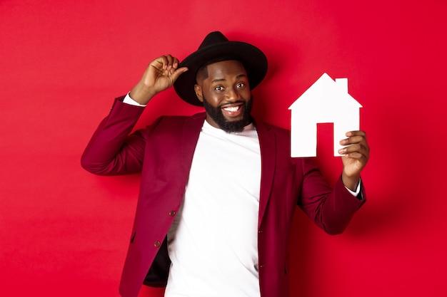 Недвижимость. веселый темнокожий мужчина показывает бумажный домик и улыбается, рекомендуя брокера, стоя на красном фоне.