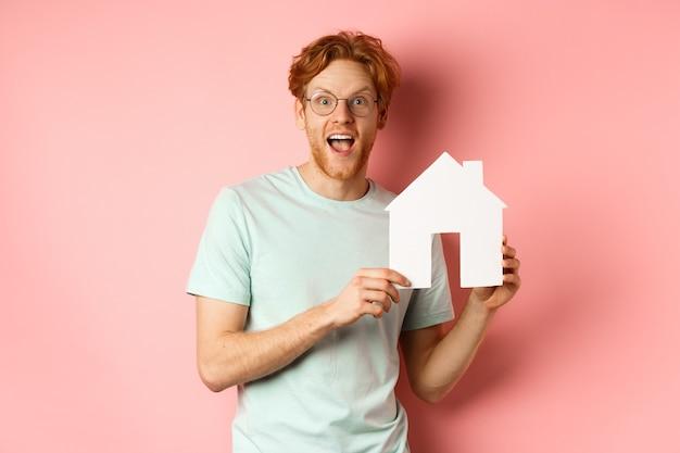 不動産。ピンクの背景の上に立って、紙の家の切り抜きを見せて、驚いて微笑んで、プロパティを購入する陽気な赤毛の男。