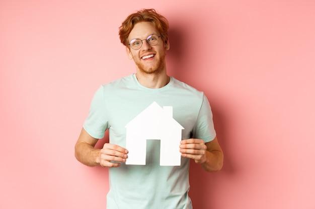 不動産。赤い髪の陽気な青年、眼鏡とtシャツを着て、紙の家の切り抜きを見せて、笑顔で、アパートを購入し、ピンクの背景。