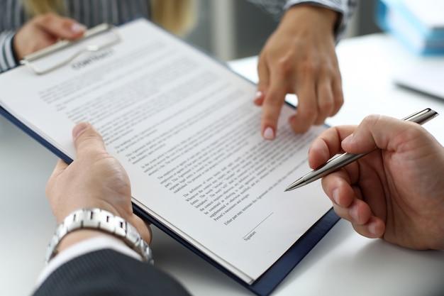Продавец недвижимости предлагает подписать документ посетителю