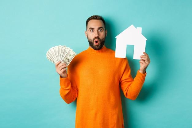 Концепция недвижимости и концепция ипотеки. пораженный покупатель, держащий деньги и бумажный дом, покупает квартиру, стоя