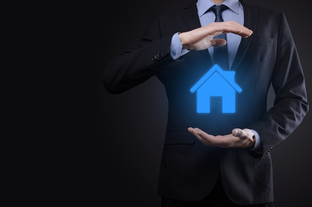 Концепция недвижимости, бизнесмен, держащий значок дома. дом в наличии. страхование имущества и концепция безопасности. защитный жест человека и символ дома.