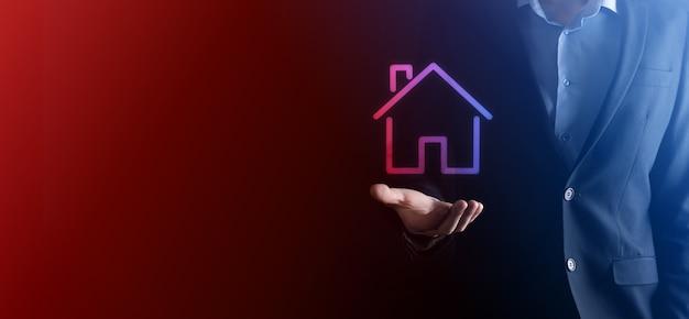 不動産のコンセプト、家のアイコンを持つビジネスマン。手持ちの家。財産保険とセキュリティのコンセプト。男の身振り手振りと家の象徴。