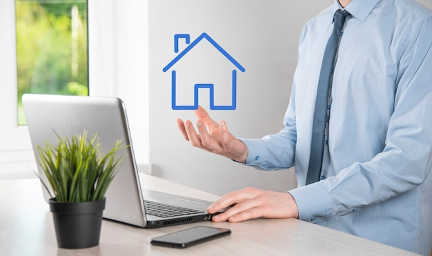 Концепция недвижимости, бизнесмен, держащий значок дома. дом на руке. страхование имущества и концепция безопасности. защитный жест человека и символ дома.