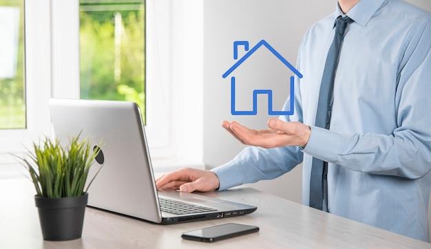 不動産の概念、家のアイコンを保持しているビジネスマン。手持ちの家。財産保険とセキュリティの概念。人間の身振りと家のシンボルを守る。