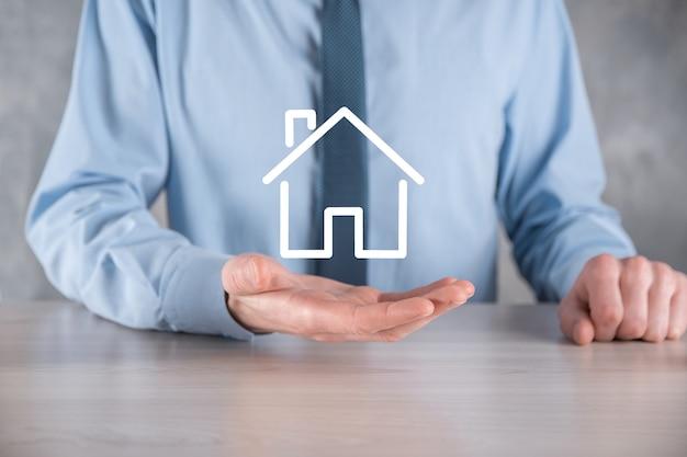 부동산 개념, 사업가 집 아이콘을 들고. hand.property 보험 및 보안 개념에 집.