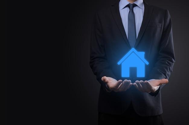 Концепция недвижимости, бизнесмен, держащий значок дома. дом на руке. страхование имущества и концепция безопасности.