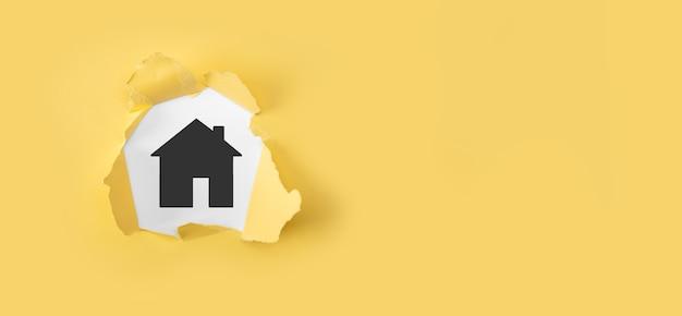 부동산 개념, 사업가 집 아이콘을 들고. 손에 집입니다. 흰색 바탕에 집 찢어진 된 노란 종이. 재산 보험 및 보안 개념입니다.