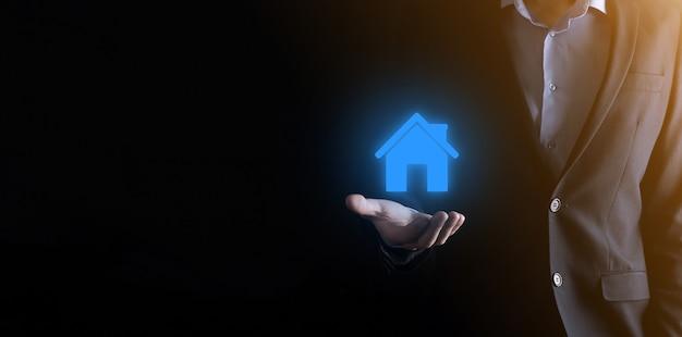 Концепция недвижимости, бизнесмен, держащий значок дома.