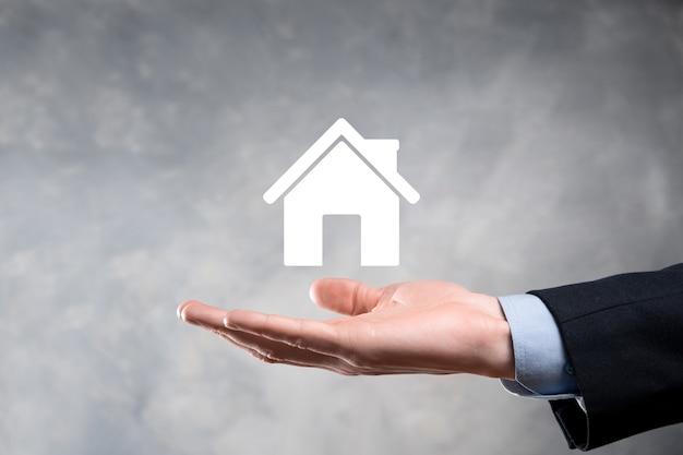 부동산 개념, 사업가 집 아이콘을 들고.