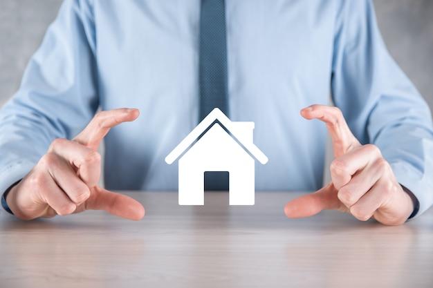 Концепция недвижимости, бизнесмен, держащий значок дома