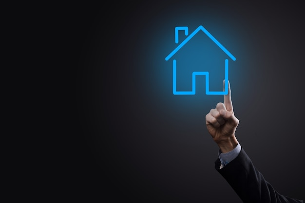 Real estate concept, businessman holding a house icon.