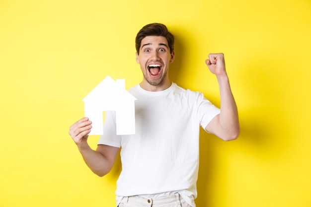 Real estate concept. cheerful man showing paper house model and making fist pump, paid mortgage, yellow background.