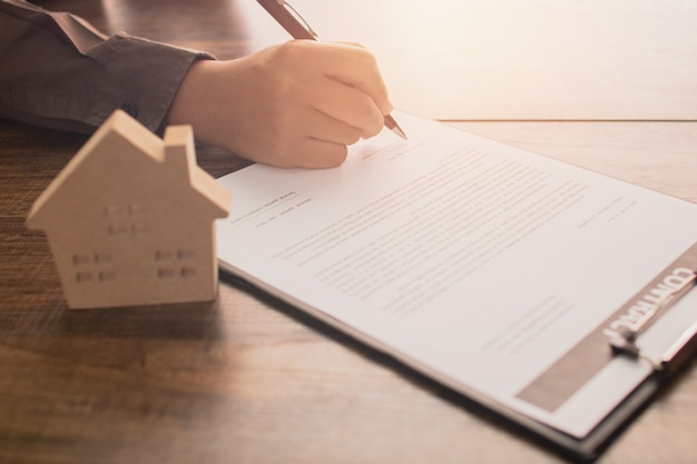 Концепция недвижимости, клиент или покупатель дома подписывают контрактную бумагу