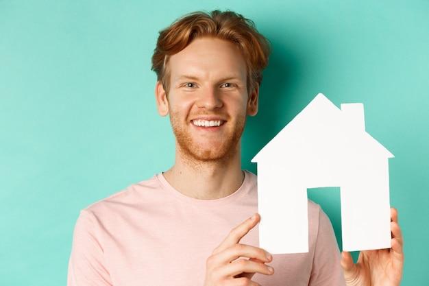 Концепция недвижимости. крупным планом рыжий бородатый мужчина в футболке с вырезом из бумажного домика, счастливый в камеру, стоящий на бирюзовом фоне