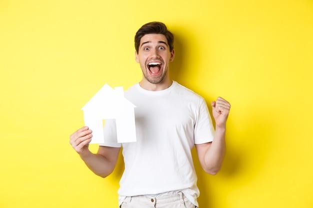 Concetto di bene immobile. uomo eccitato che tiene modello di casa di carta e festeggia, in piedi felice su sfondo giallo.