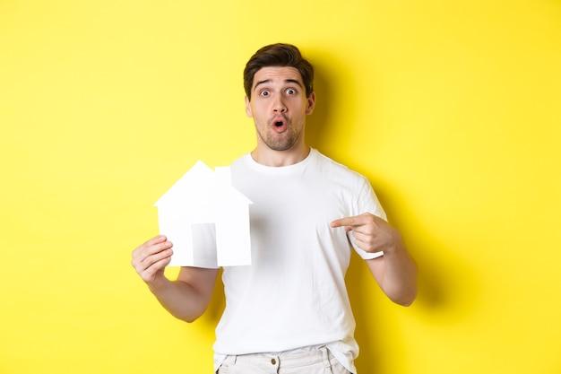 不動産のコンセプト。黄色の背景の上に立って、フラットを探して、紙の家のモデルに指を指している興奮した男。