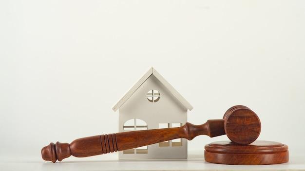 Концепция недвижимости: молоток и блок с игрушечным домиком