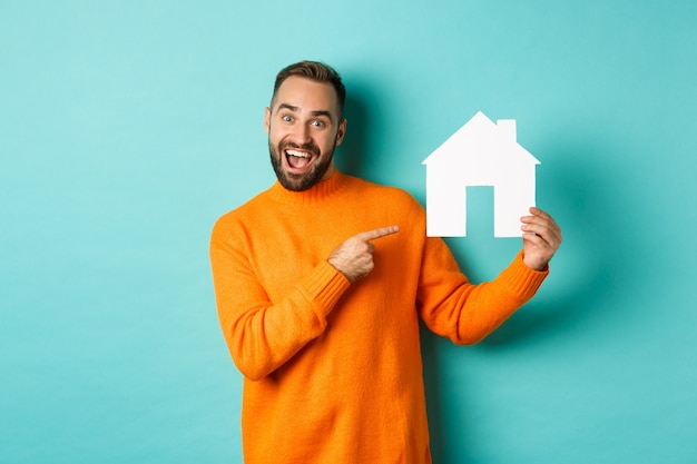 Real estate concept. happy man pointing finger at paper home maket and smiling, standing over light blue background.