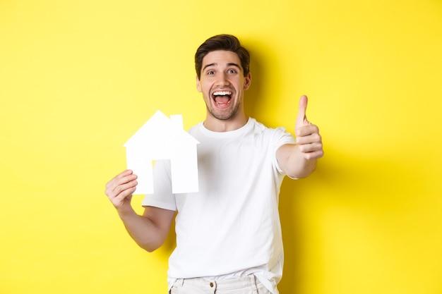不動産のコンセプト。幸せな若い男性のバイヤーは、親指を立てて、紙の家のモデルを示し、満足して笑って、黄色の背景の上に立っています。