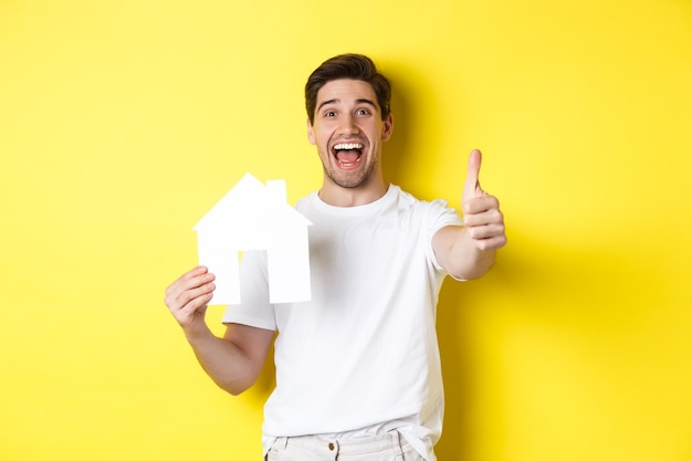 Real estate concept. happy young male buyer showing thumb up and paper house model, smiling satisfied, standing over yellow background.