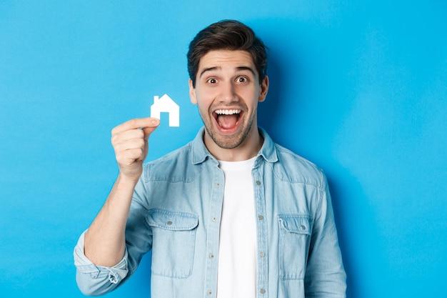 Concetto di bene immobile. felice giovane che sembra eccitato, ha trovato un appartamento, mostrando il modello di una piccola casa, in piedi su sfondo blu