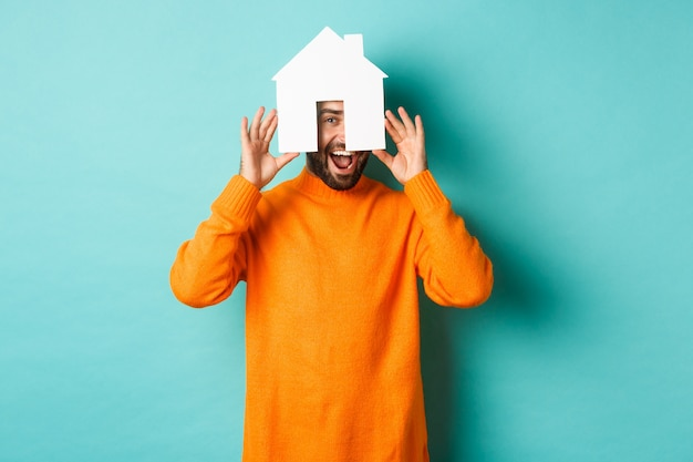 Real estate concept. happy young man searching for home rent, holding house paper maket and smiling, standing over blue background.