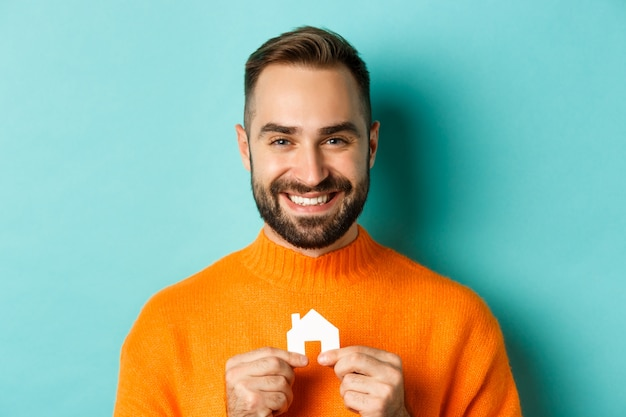 Real estate concept. happy young man searching for home rent, holding paper house smiling