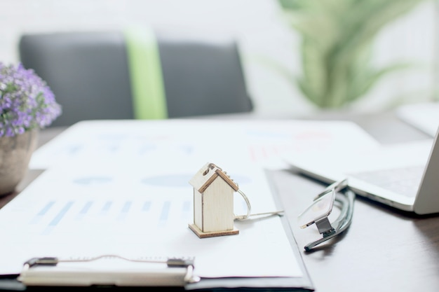 부동산 개념, 테이블에 홈 키와 금융 종이에 집 모델