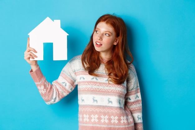 Concetto di bene immobile. immagine di una ragazza rossa carina che guarda curiosa al modello di una casa di carta, pensando di acquistare proprietà, in piedi in un maglione su sfondo blu.