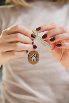 女性の手に家の形をしたキーホルダーと不動産のコンセプトキー
